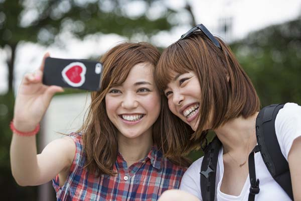 Kyoto,Japan,Two women, friends, taking a selfie in the park.